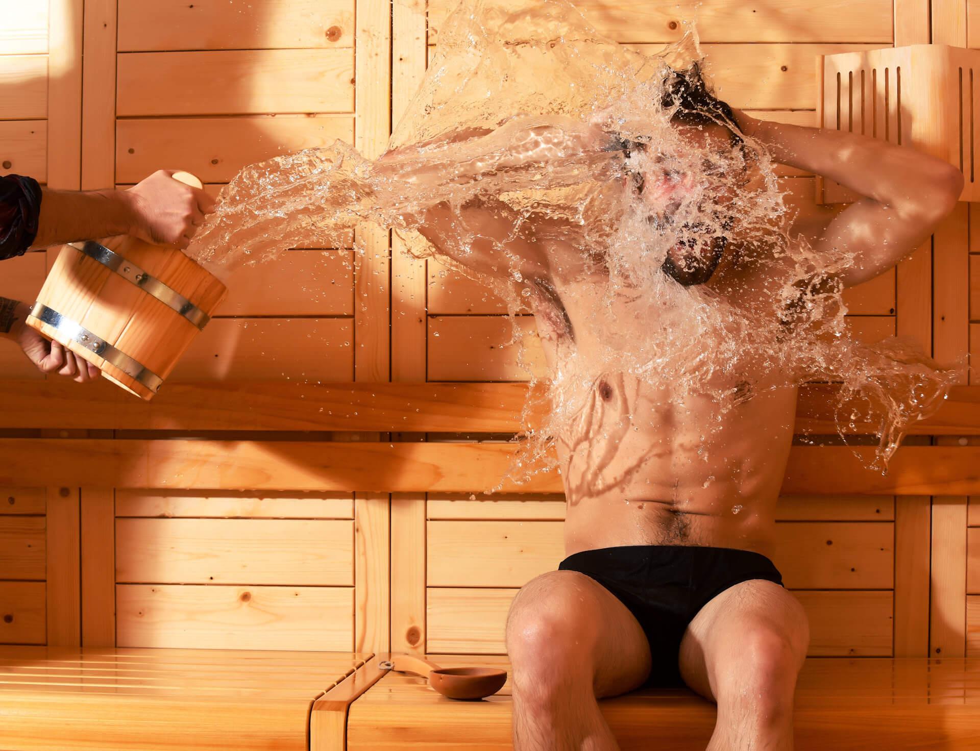 Mężczyzna siedzący w saunie oblewany wodą