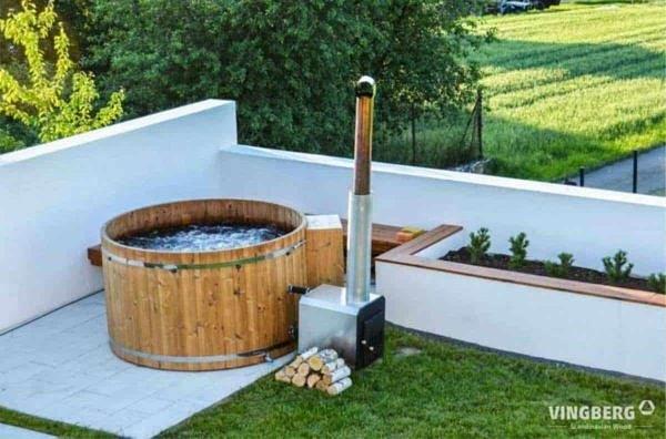 Balia Norra #185 ThermoWood® z piecem zewnętrznym opalanym drewnem, z systemem jacuzzi w otoczeniu ogrodu.