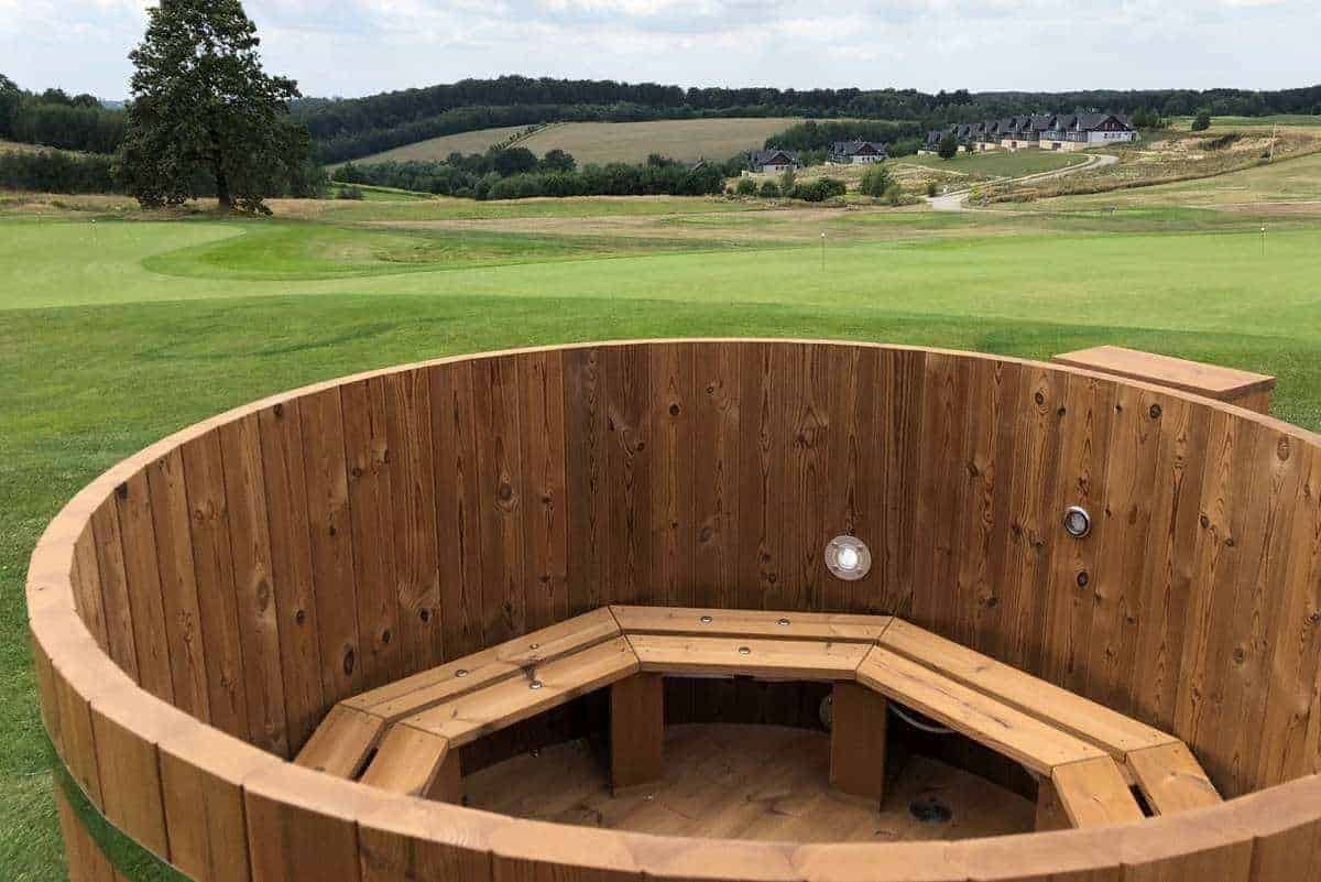 Drewniana balia ogrodowa ThermoWood® Vingberg. W tle widok na pole golfowe