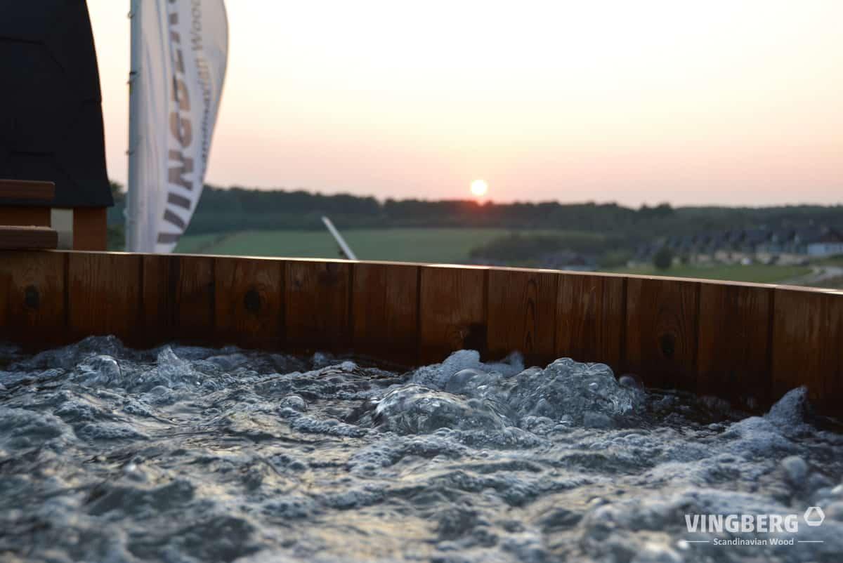 Drewniana balia ogrodowa z wodą na tle zachodzącego słońca