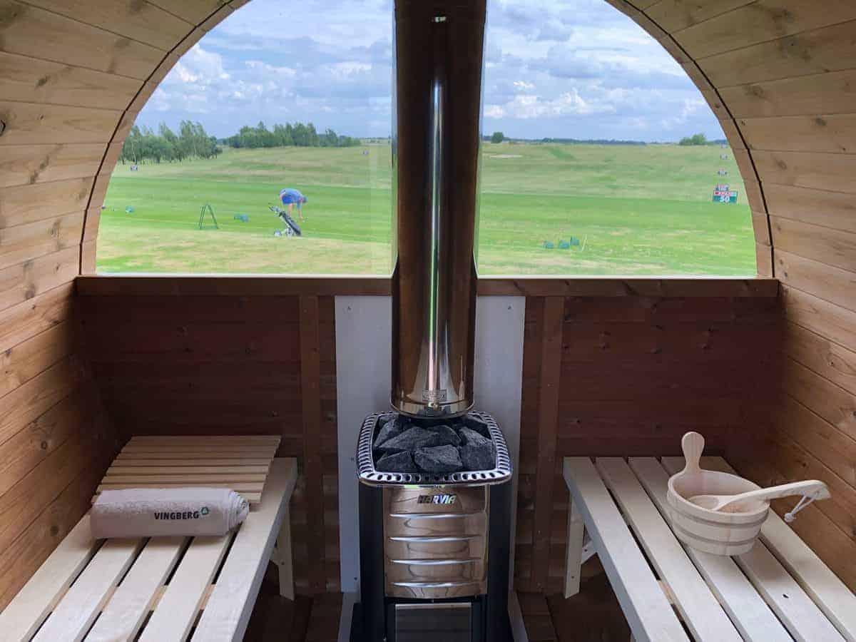 Wnętrze sauny ogrodowej Akka #280 Vingberg ThermoWood® z oknem panoramicznym. W tle pole golfowe