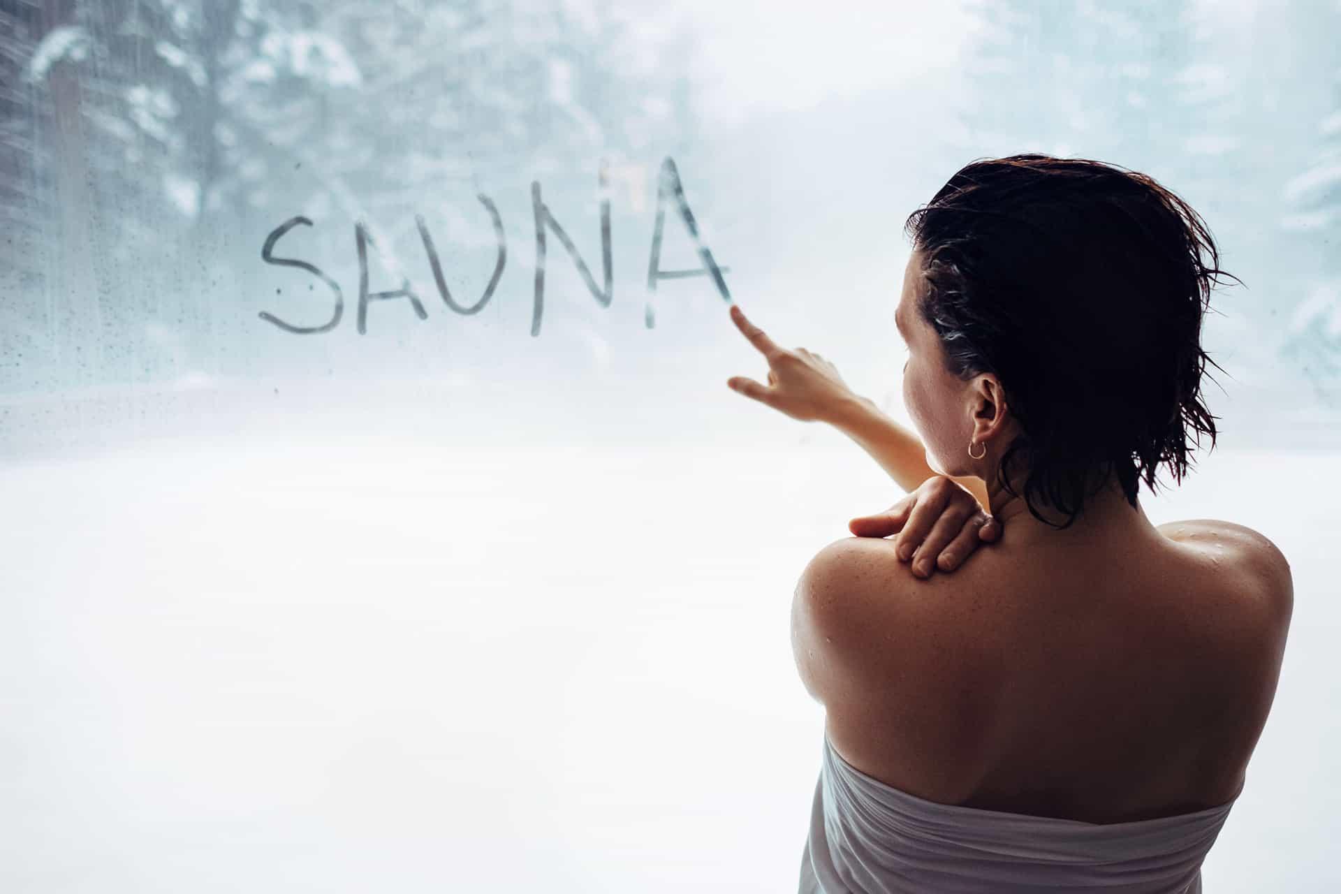 """Kobieta pisząca słowo""""sauna""""na szybie"""
