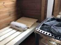 Wnętrze sauny Akka #280 firmy Vingberg. Widoczny piec opalany drewnem (Harvia M3)