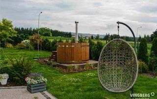 Balia Norra #185 ThermoWood® z piecem zewnętrznym opalanym drewnem w otoczeniu ogrodu.